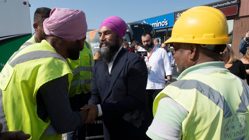 NDP leader Jagmeet Singh speaks with construction workers who stopped doing road work to listen to his speech during a campaign announcement in Essex, Ont. Friday September 20, 2019. THE CANADIAN PRESS/Adrian Wyld