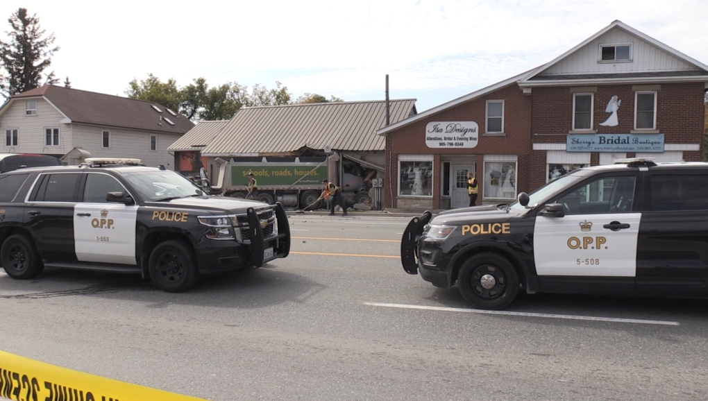 Dump truck smashes into multiple cars and building