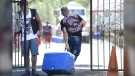 Nova Scotia RCMP say they will be monitoring a large gathering of outlaw bike gangs on Saturday in the Annapolis Valley. A member of the Red Devils motorcycle club carries a cooler into the the Hells Angels Nomads compound before the group's Canada Run event in Carlsbad Springs, Ont., near Ottawa, Friday, July 22, 2016. (THE CANADIAN PRESS/Justin Tang)