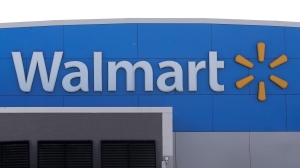 In this Sept. 3, 2019 file photo, a Walmart logo is displayed outside of a Walmart store, in Walpole, Mass. Walmart says it will stop selling electronic cigarettes at its namesake stores and Sam's Clubs following a string of illnesses and deaths related to vaping. The nation's largest retailer said Friday, Sept. 20 that it will complete its exit from e-cigarettes after selling through current inventory. It cited growing federal, state and local regulatory complexity regarding vaping products. (AP Photo/Steven Senne, File)