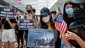 Pro-democracy university students hold U.S. flags and placards at the campus of the University of Hong Kong, Friday, Sept. 20, 2019, as they demand the U.S. Congress to pass the proposed U.S. Act of the Hong Kong Human Rights and Democracy.  (AP Photo/Kin Cheung)