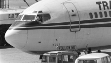 A Shiite Moslem hijacker points his pistol toward an ABC news media crew from the window of the cockpit of the Trans World Airlines jet as the American television crew approaches the jet for an interview at Beirut International Airport, Lebanon, Wednesday, June 19, 1985. (AP Photo/Herve Merliac/FILE)