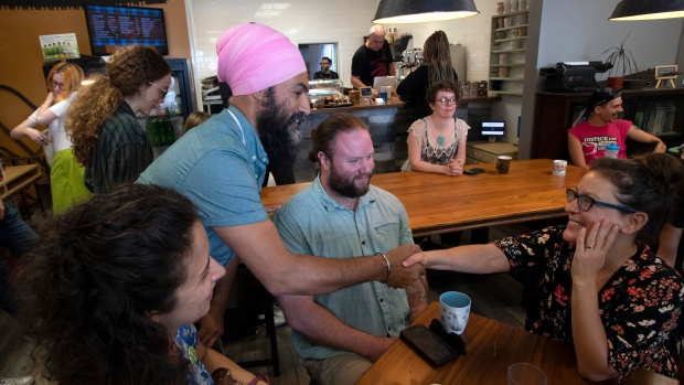 NDP Leader Jagmeet Singh shakes hands with supporters during a a campaign stop at a coffee shop in Toronto, Saturday, Sept. 21, 2019. THE CANADIAN PRESS/Adrian Wyld