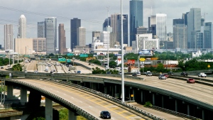 A realtor who has delivered 15,000 brochures promoting Texas as a corporate headquarters location in western Canada says they have helped around 100 western Canadian companies move north of Houston in the last decade and forty of those were in the past year and a half. Cars travel along a highway with the skyline of downtown Houston in the background on May 20, 2010. (THE CANADIAN PRESS / AP-Houston Chronicle, Michael Paulsen)