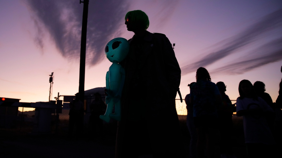 """Chase Hansen holds an inflatable alien near an entrance to the Nevada Test and Training Range near Area 51, Friday, Sept. 20, 2019, near Rachel, Nev. People came to visit the gate inspired by the """"Storm Area 51"""" internet hoax. (AP Photo/John Locher)"""