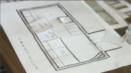 Plans are shown to build a tiny house, at a building workshop.