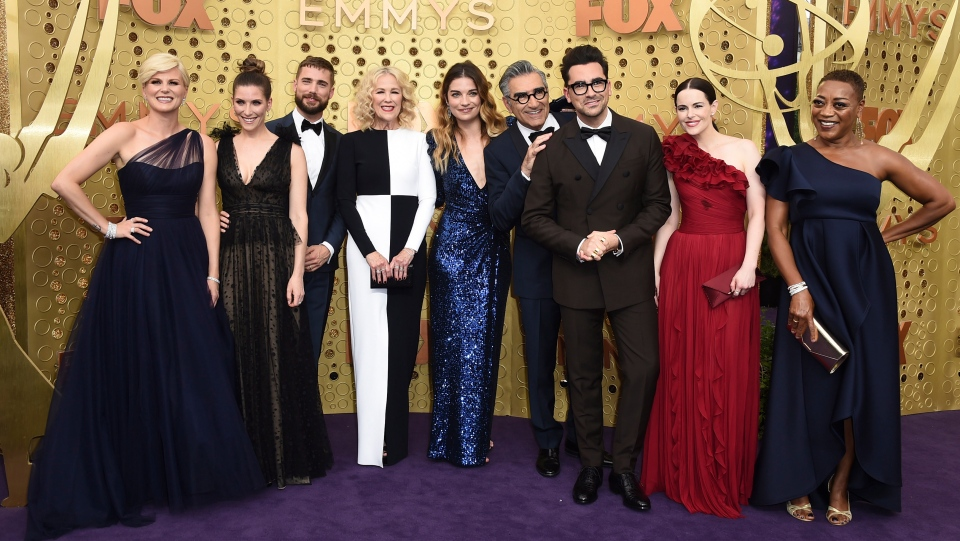 "Jennifer Robertson, from left, Sarah Levy, Dustin Milligan, Catherine O'Hara, Annie Murphy, Eugene Levy, Daniel Levy, Emily Hampshire, Karen Robinson, from the cast of ""Schitt's Creek,"" arrive at the 71st Primetime Emmy Awards on Sunday, Sept. 22, 2019, at the Microsoft Theater in Los Angeles. (Photo by Jordan Strauss/Invision/AP)"