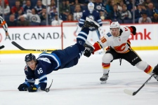 Winnipeg Jets' Joona Luoto (46) is tripped by Calgary Flames' Andrew Mangiapane (88) during second period NHL pre-season action in Winnipeg on Sunday, Sept. 22, 2019. (THE CANADIAN PRESS/Fred Greenslade)