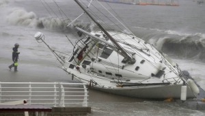 In this Sunday, Sept. 22, 2019, photo, a yacht is pushed ashore by strong winds and high waves at a beach as Typhoon Tapah approaches in Ulsan, South Korea. (Kim Yong-tae/Yonhap via AP)