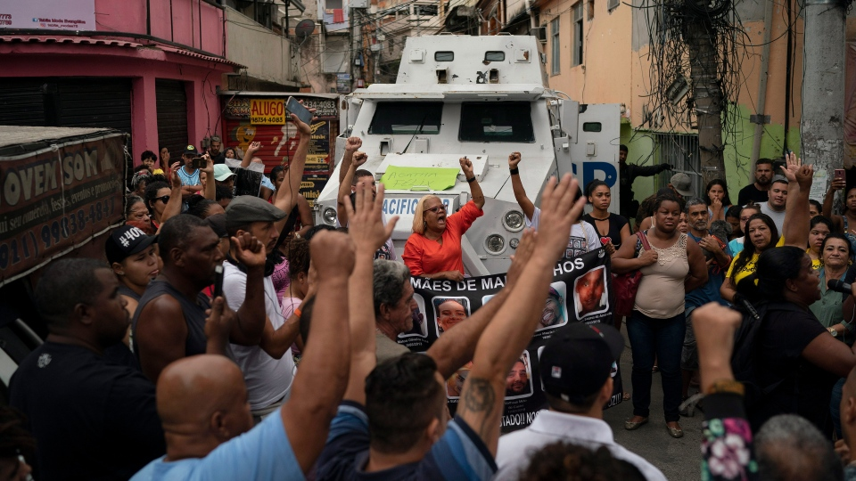 "People chant ""Agatha lives"" in front of a police armored vehicle during a protest at the site where 8-year-old Agatha Sales Felix was killed by a stray bullet, at the Alemao complex slum in Rio de Janeiro, Brazil, Saturday, Sept. 21, 2019. (AP Photo/Leo Correa)"