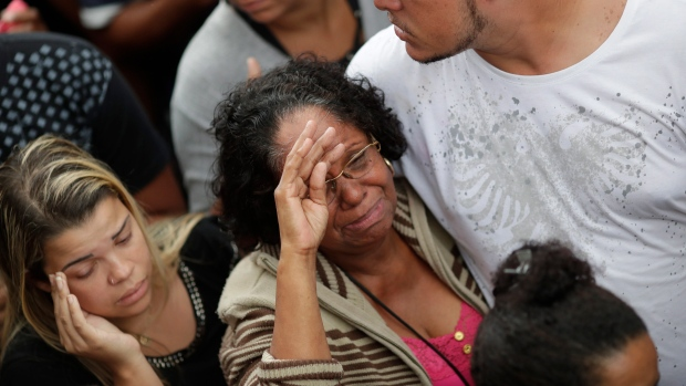 The grandmother of the late 8-year-old Ágatha Sales Felix cries during her granddaughter's burial at the cemetery in Rio de Janeiro, Brazil, Sunday, Sept. 22, 2019. (AP Photo/Silvia Izquierdo)