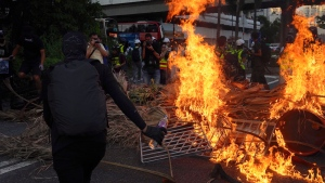 A protester sets fire to a barricade during a protest in Hong Kong on Sunday, Sept. 22, 2019. Hong Kong's pro-democracy protests, now in their fourth month, have often descended into violence late in the day and at night. (AP Photo/Vincent Yu)