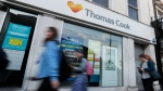 People walk past a closed Thomas Cook travel shop in London, Monday, Sept. 23, 2019. (AP Photo/Frank Augstein)