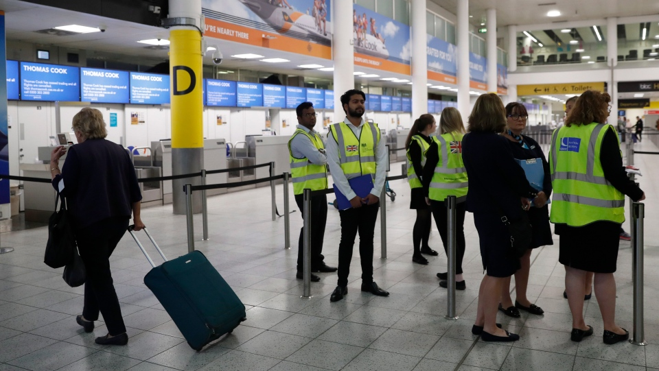 British Foreign Office personnel, with a team from Gatwick airport stand by the entrance to Thomas Cook check-in desks in Gatwick Airport, England Monday, Sept. 23, 2019. (AP Photo/Alastair Grant)