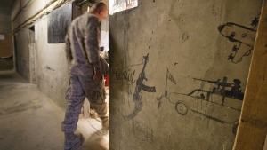 Taliban graffiti shows an AK-47 assault rifle and the word 'Allah' at left, along with Taliban fighters at right, decorating a wall in the Musa Qala district centre in Helmand province, Afghanistan, on July 25, 2011. (David Goldman / AP)
