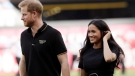 FILE - In this Saturday, June 29, 2019 file photo, Britain's Prince Harry, left, and Meghan, Duchess of Sussex, walk off the field before a baseball game in London. Royal officials say Prince Harry will see the legacy of his late mother Princess Diana's humanitarian work in Angola during a visit to southern Africa this fall. Buckingham Palace released details Friday, Sept. 6 of the trip by Harry, Meghan and their son Archie, who was born in May. (AP Photo/Tim Ireland, file)