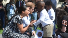 Prince Harry and Meghan Duchess of Sussex, greet children on their arrival at the Nyanga Methodist Church in Cape Town, South Africa, Monday, Sept, 23, 2019. (Courtney Africa / Africa News Agency via AP, Pool)