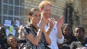 Prince Harry and Meghan Duchess of Sussex, greet youths on a visit to the Nyanga Methodist Church in Cape Town, South Africa, Monday, Sept, 23, 2019. (Courtney Africa / Africa News Agency via AP, Pool)