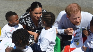 Prince Harry and Meghan, Duchess of Sussex, greet children on their arrival at the Nyanga Methodist Church in Cape Town, South Africa, Monday, Sept, 23, 2019. (Courtney Africa / Africa News Agency via AP, Pool)