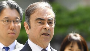 Former Nissan chairman Carlos Ghosn, centre, arrives at Tokyo District Court, on May 23, 2019. (Ren Onuma / Kyodo News via AP, File)