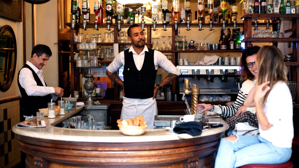 Waiters Jean Baptiste Magnique, centre, and Didier Hubert talks with customer of the cafe 'Au petit Fer a Cheval' (The small horseshoe), in the historical Marais district of Paris, Thursday, Sept. 19, 2019. Stepping into the over a century-old Le Petit Fer à Cheval bistrot café-restaurant, named after it's horseshoe-shaped bar, is like traveling back in time. (AP Photo/Thibault Camus)