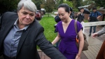 Huawei chief financial officer Meng Wanzhou, right, who is out on bail and remains under partial house arrest after she was detained last year at the behest of American authorities, is escorted by a member of a private security team as she leaves her home to attend a court hearing in Vancouver, on Monday Sept. 23, 2019. THE CANADIAN PRESS/Darryl Dyck