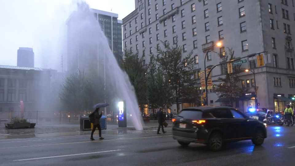 A water main burst in downtown Vancouver, sending a stream of water shooting into the sky.