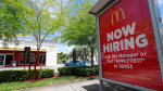 "In this Monday, July 1, 2019, file photo, a ""Now Hiring"" sign appears on a bus stop in front of a McDonald's restaurant in Miami. (AP Photo/Wilfredo Lee, File)"