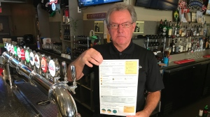 Arthur Ewing, owner of sports bar Ace's Place in Scarborough, holds up a Toronto hydro bill. (Pat Foran/CTV News Toronto)