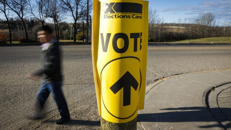 A voter walks past a sign directing voters to a polling station for the Canadian federal election in Cremona, Alta., on Oct. 19, 2015. (THE CANADIAN PRESS / Jeff McIntosh)
