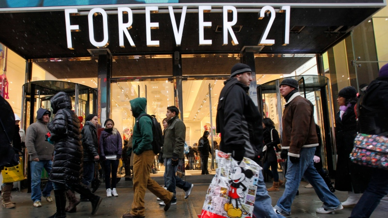 FILE - In this Dec. 26, 2010 file photo, people walk past a Forever 21 store in New York's Times Square. (AP Photo/Mary Altaffer, file)
