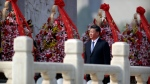 Chinese President Xi Jinping walks past floral wreaths at the Monument to the People's Heroes during a ceremony to mark Martyr's Day at Tiananmen Square in Beijing, Monday, Sept. 30, 2019. (AP Photo/Mark Schiefelbein, Pool)
