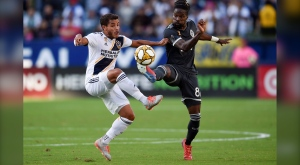 LA Galaxy midfielder Jonathan dos Santos, left, and Vancouver Whitecaps FC forward Tosaint Ricketts battle for the ball during the first half of an MLS soccer match in Carson, Calif., Sunday, Sept. 29, 2019. (AP Photo/Kelvin Kuo)
