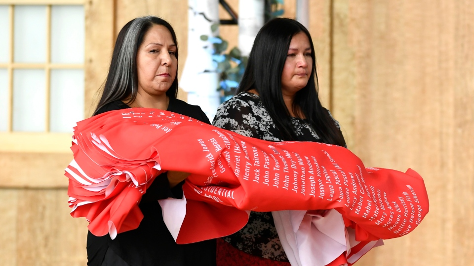 Joyce Hunter, right, whose brother Charlie Hunter died at St. Anne's Residential School in 1974, and Stephanie Scott, staff at the National Centre for Truth and Reconciliation, lay down a ceremonial cloth with the names of 2,800 children who died in residential schools and were identified in the National Student Memorial Register, on Monday, Sept. 30, 2019. THE CANADIAN PRESS/Justin Tang