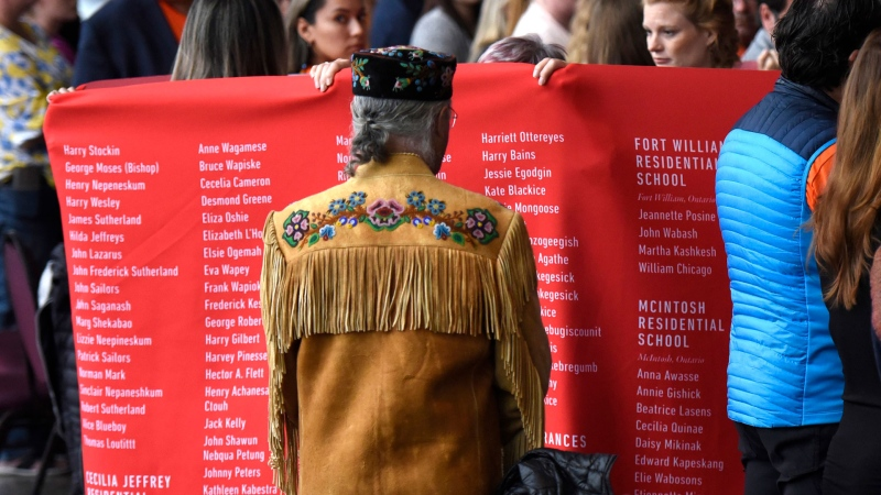 Clement Chartier, president of the Metis National Council, watches as a ceremonial cloth with the names of 2,800 children who died in residential schools and were identified in the National Student Memorial Register, is carried to the stage during the Honouring National Day for Truth and Reconciliation ceremony in Gatineau, Quebec on Monday, Sept. 30, 2019. (THE CANADIAN PRESS / Justin Tang)