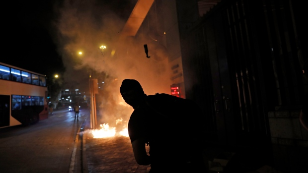 Police fire tear gas shell as a fire burns outside a police station in Hong Kong, Wednesday, Oct. 2, 2019. (AP Photo/Kin Cheung)