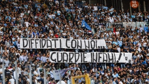 """In this Oct. 1, 2017 file photo, Lazio fans display a banner reading in Italian """"Banned fans with us, vile cops"""" during a Serie A soccer match between Sassuolo and Lazio at the Olympic stadium in Rome. Lazio fans have a long history of racism and anti-Semitism but the Roman club's supporters established a new low on Sunday, Oct. 22, 2017 when they littered the Stadio Olimpico with superimposed images of Anne Frank - the young diarist who died in the Holocaust - wearing a Roma jersey. (Angelo Carconi/ANSA via AP, files)"""