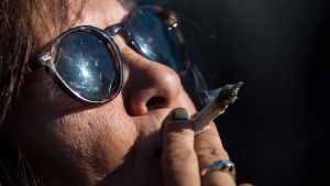 A woman smokes marijuana while celebrating the legalization of recreational cannabis, in Vancouver, on Wednesday October 17, 2018. (THE CANADIAN PRESS / Darryl Dyck)