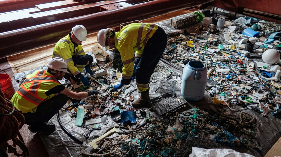 In this undated handout photo provided by The Ocean Clean Up, crew members sort through plastic on board a support vessel on the Pacific Ocean. (The Ocean Cleanup via AP)