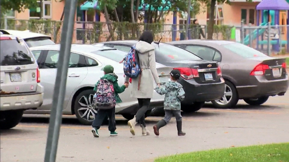 A parent is seen walking her children into school. (File image)
