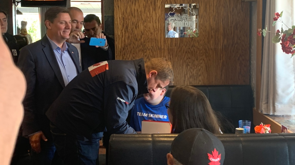 Conservative Leader Andrew Scheer chats with 12-year-old Chris Carson during a campaign stop in Peterborough, Ont. on Saturday, Oct. 5, 2019.