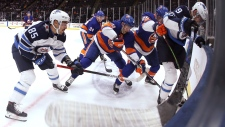 Winnipeg Jets center Andrew Copp (9) fights for possession against New York Islanders defenseman Devon Toews (25), center Derick Brassard (10) and defenseman Scott Mayfield (24) during the first period of an NHL hockey game Sunday, Oct. 6, 2019, in Uniondale, N.Y. (AP Photo/Michael Owens)