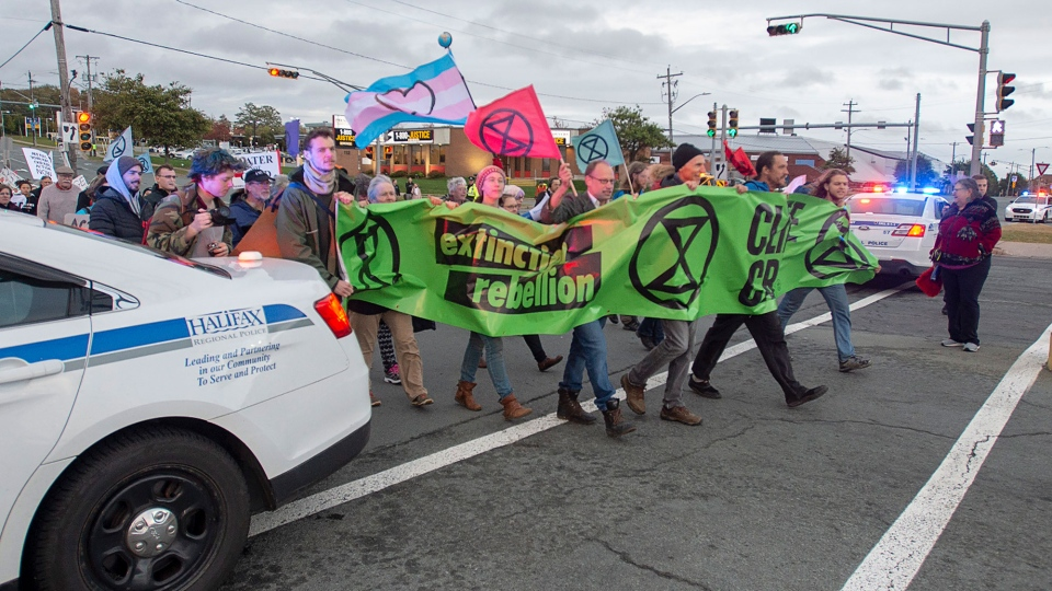 Members of Extinction Rebellion, protesting issues related to climate change, march to the Angus L. Macdonald Bridge in Dartmouth, N.S. on Monday, Oct. 7, 2019. The bridge was closed to all traffic in early morning rush hour. Protests are expected in other Canadian cities including Burrard Street Bridge in Vancouver and Prince Edward Viaduct in Toronto. THE CANADIAN PRESS/Andrew Vaughan