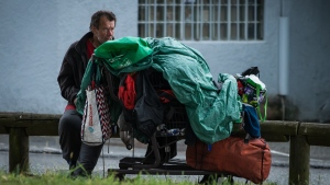A homeless man sits with a cart of belongings in Surrey, B.C., on Sunday July 7, 2019. THE CANADIAN PRESS/Darryl Dyck