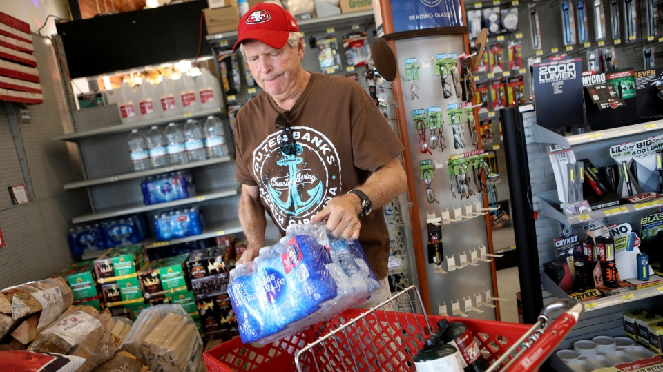 James Cooke is shown buying water bottles along with propane tanks and batteries at a ACE Hardware store as he prepares for a possible power shutdown in Los Gatos, Calif., on Tuesday, Oct. 8, 2019. (Anda Chu/San Jose Mercury News via AP)
