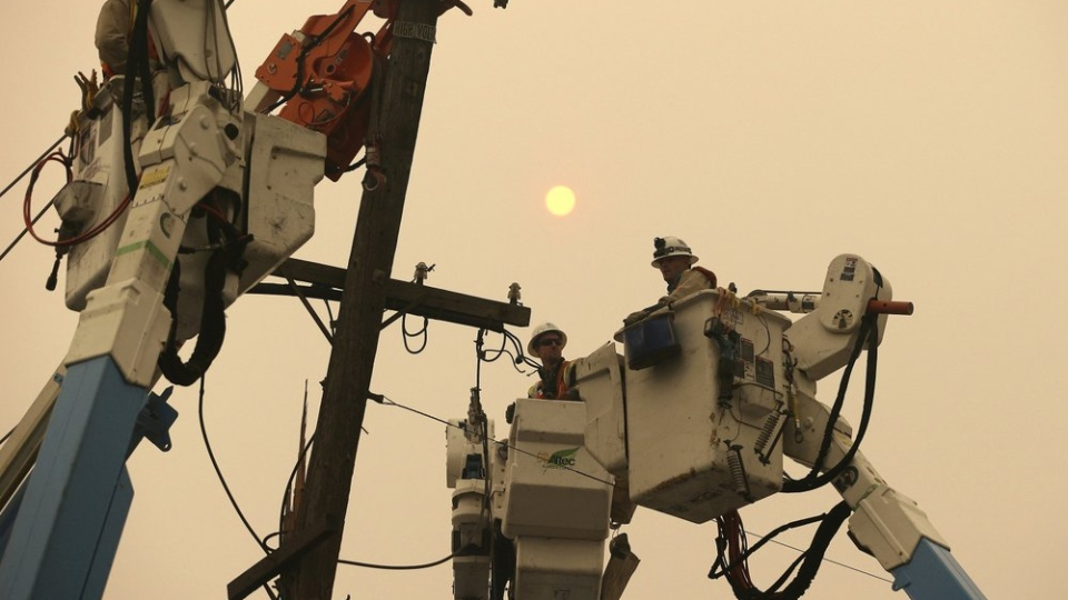 FILE - In this Nov. 9, 2018, file photo, Pacific Gas & Electric crews work to restore power lines in Paradise, Calif. (AP Photo/Rich Pedroncelli, File)