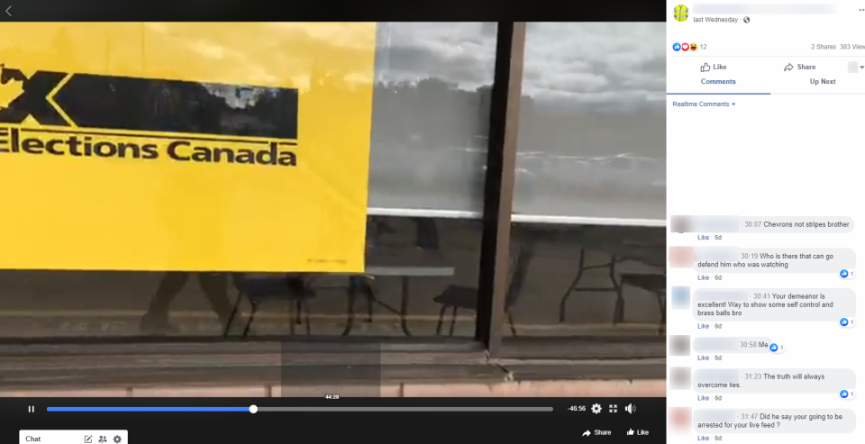 An image taken from a livestream video posted on Facebook Oct. 2, shows the reflection of a man wearing a yellow vest who has camped outside an Elections Canada office in Orillia, Ont. on several occasions over the past week. He has elicited warnings from police that he could face mischief charges if he engages with people entering or leaving or films through the windows.