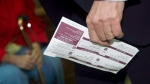 A man carries his voter identification card in this file photo. (The Canadian Press/Nathan Denette)
