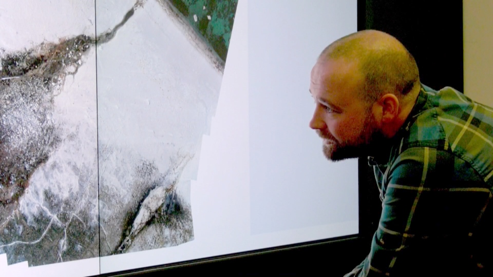 Arctic Institute researcher Matt Ayre looks at photos of the site.