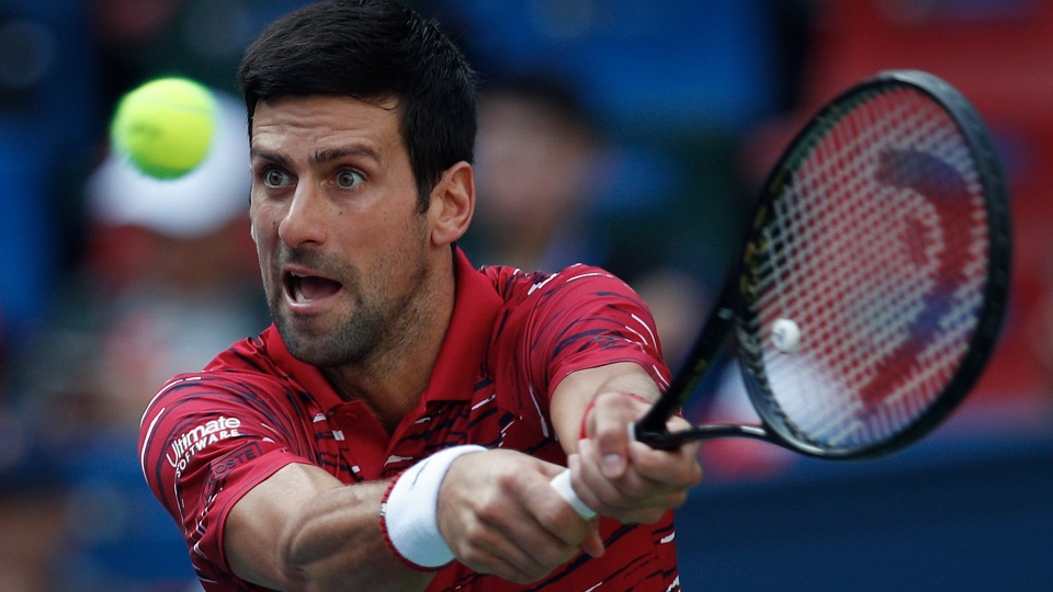 Novak Djokovic of Serbia hits a return shot against John Isner of the United States during their men's singles match at the Shanghai Masters tennis tournament at Qizhong Forest Sports City Tennis Center in Shanghai, China, Thursday, Oct. 10, 2019. (AP Photo/Andy Wong)